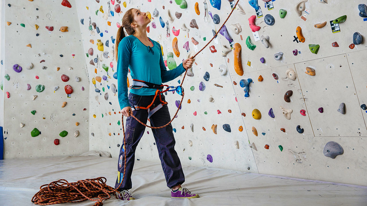 Frau vor Indoor-Kletterwand für Disaster Recovery Konzept