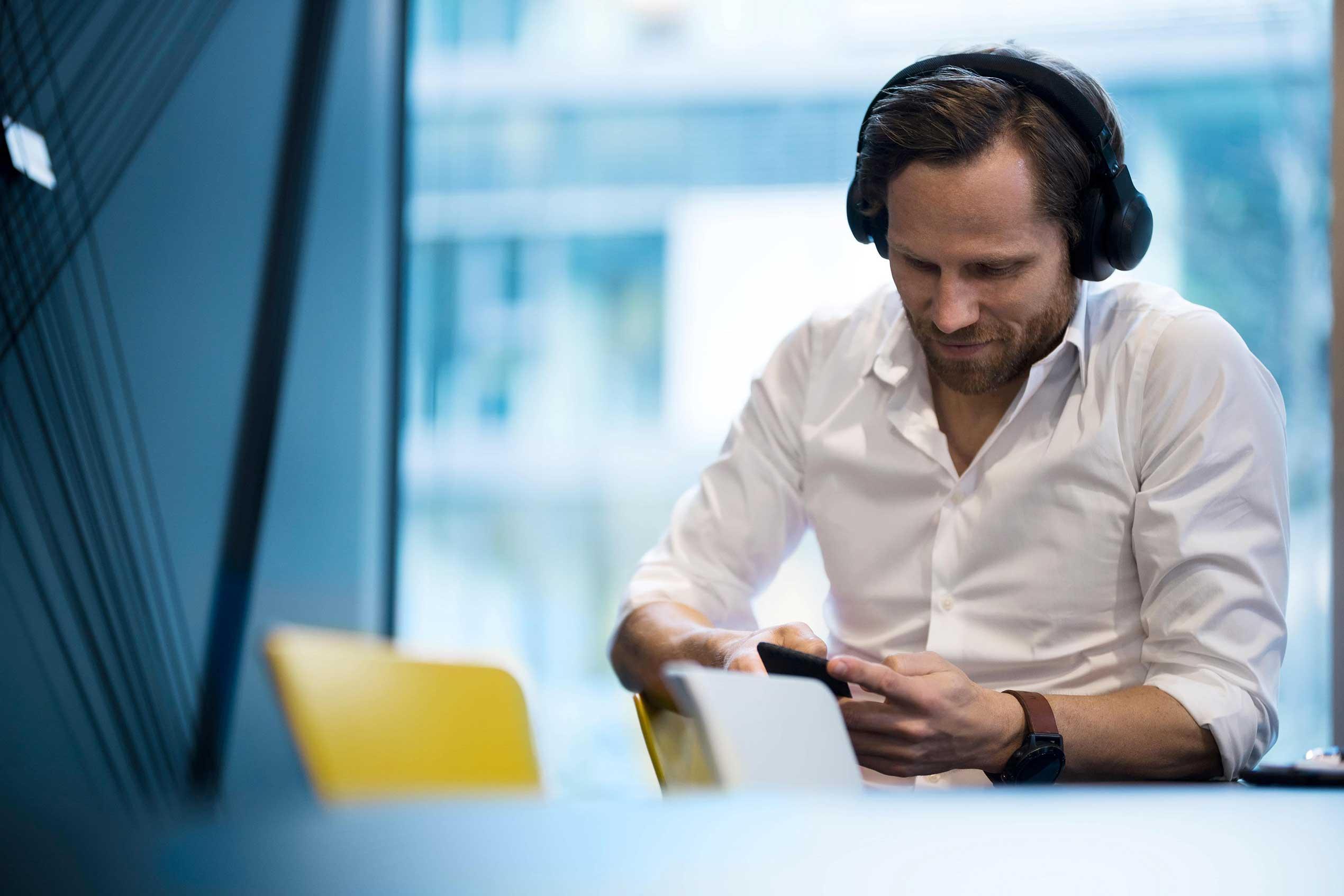 Mann mit Kopfhörern benutzt sein Handy für APA-Basisdienst