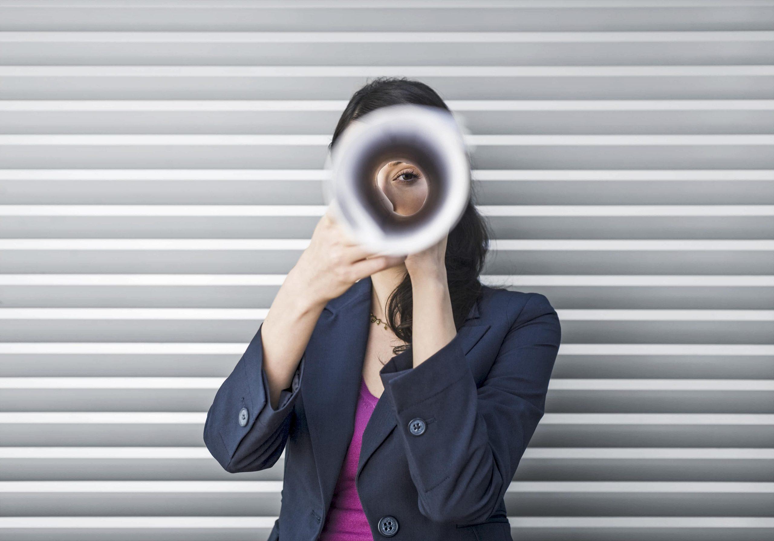 Frau sieht durch gerollte Zeitung für Mediendatenbank