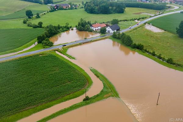 Auf dem Foto sieht man ein überschwemmtes Feld. Ein Straße geht durch das Wasser.