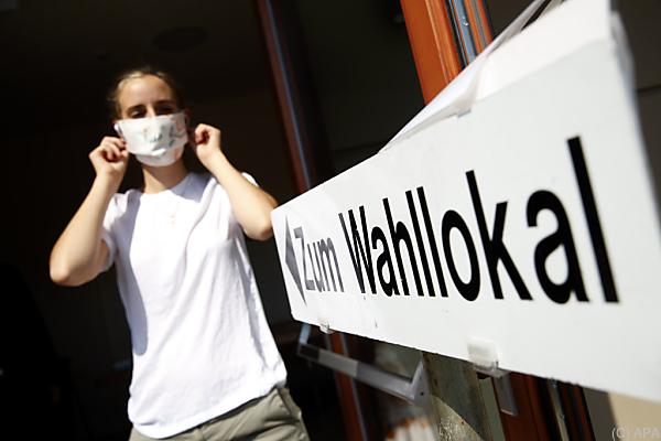Auf dem Foto sieht man eine Frau mit Schutzmaske vor einem Wahllokal in der Steiermark.