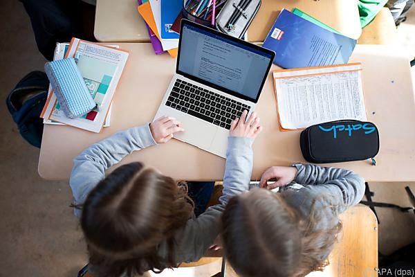 Auf dem Bild sieht man 2 Kinder von oben. Sie benutzen einen tragbaren Computer.