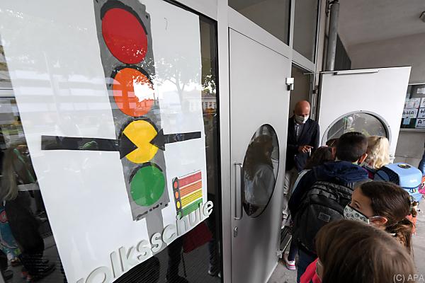 Auf dem Bild sieht man eine Corona-Ampel. Sie ist an einem Schultor befestigt. Die Ampel hat 4 Farben: Grün, Gelb, Orange und Rot.