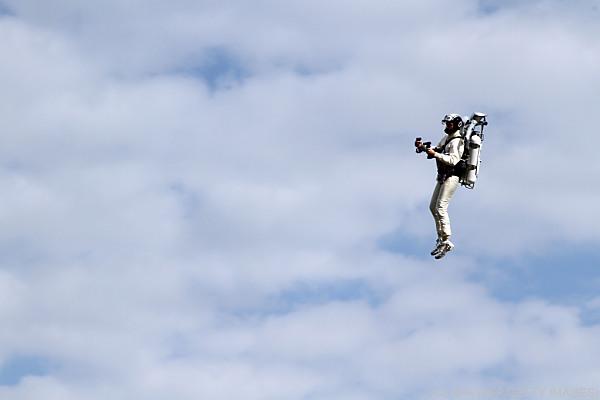 Auf dem Foto sieht man einen Mann, der mit einen Jetpack fliegt.