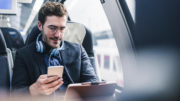 Mann mit Kopfhörer, Notebook und Handy im Zug für Videoproduktion und Verbreitung