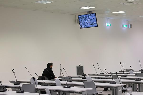 Auf dem Bild sieht man einen Gerichts-Saal. Darin sitzt ein Anwalt.