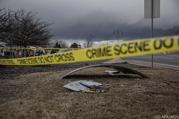 Auf dem Bild sieht Teile von einem Flugzeug am Boden verstreut. Absperrbänder von der Polizei hindern die Menschen am Betreten des Fundortes.