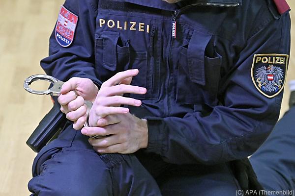 Auf dem Bild sieht man einen Polizisten, der jemandem Handschellen anlegt.