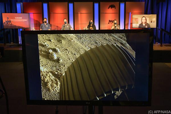 Auf dem Bild sieht man Mitarbeiter der NASA und ein Bild von einem Reifen des Roboters