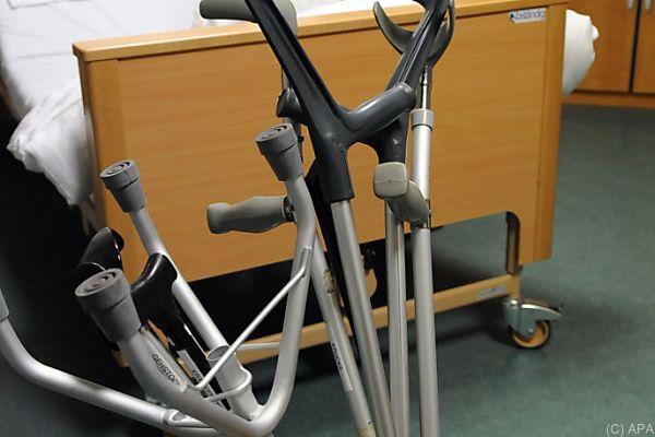 Auf dem Bild sieht man eine Pensionistin in einem Krankenbett. Davor stehen Krücken und Geh-Hilfen.