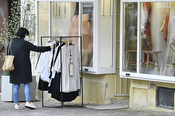 Auf dem Bild sieht man eine Frau vor einem Mode-Geschäft.