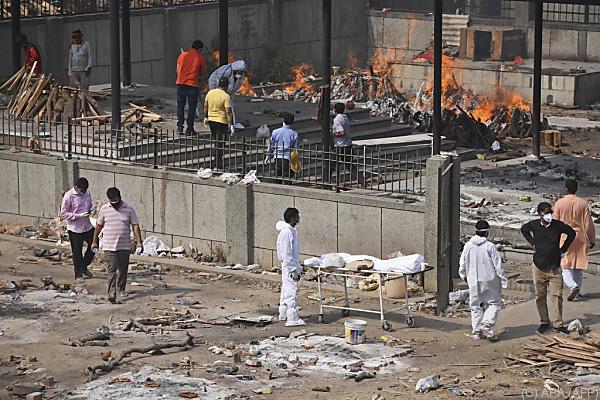 Auf dem Bild sieht man eine Straße in Indien. Corona-Tote werden dort verbrannt.