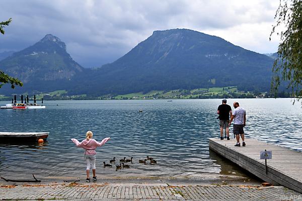 Auf dem Foto sieht man einige Urlauber am Ufer des Wolfgangsees.