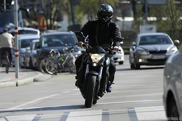 Auf dem Foto sieht man einen Motorradfahrer in der Stadt fahren.