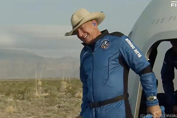 Auf dem Bild sieht man, wie Jeff Bezos nach geglückter Landung auf der Erde aus der Raumkapsel steigt.
