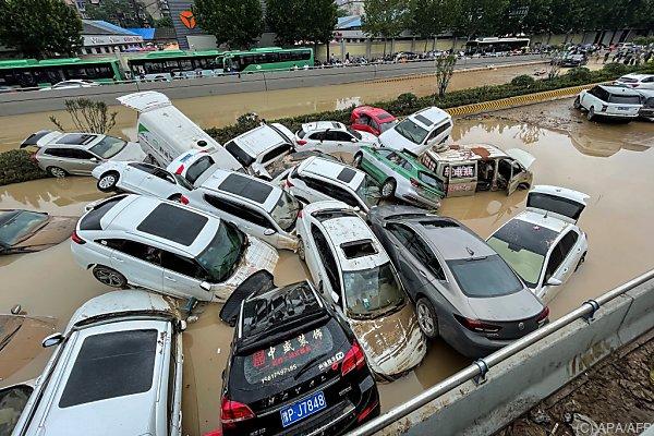 Auf dem Bild sieht man Autos, die von der Überschwemmung ineinander verkeilt wurden.
