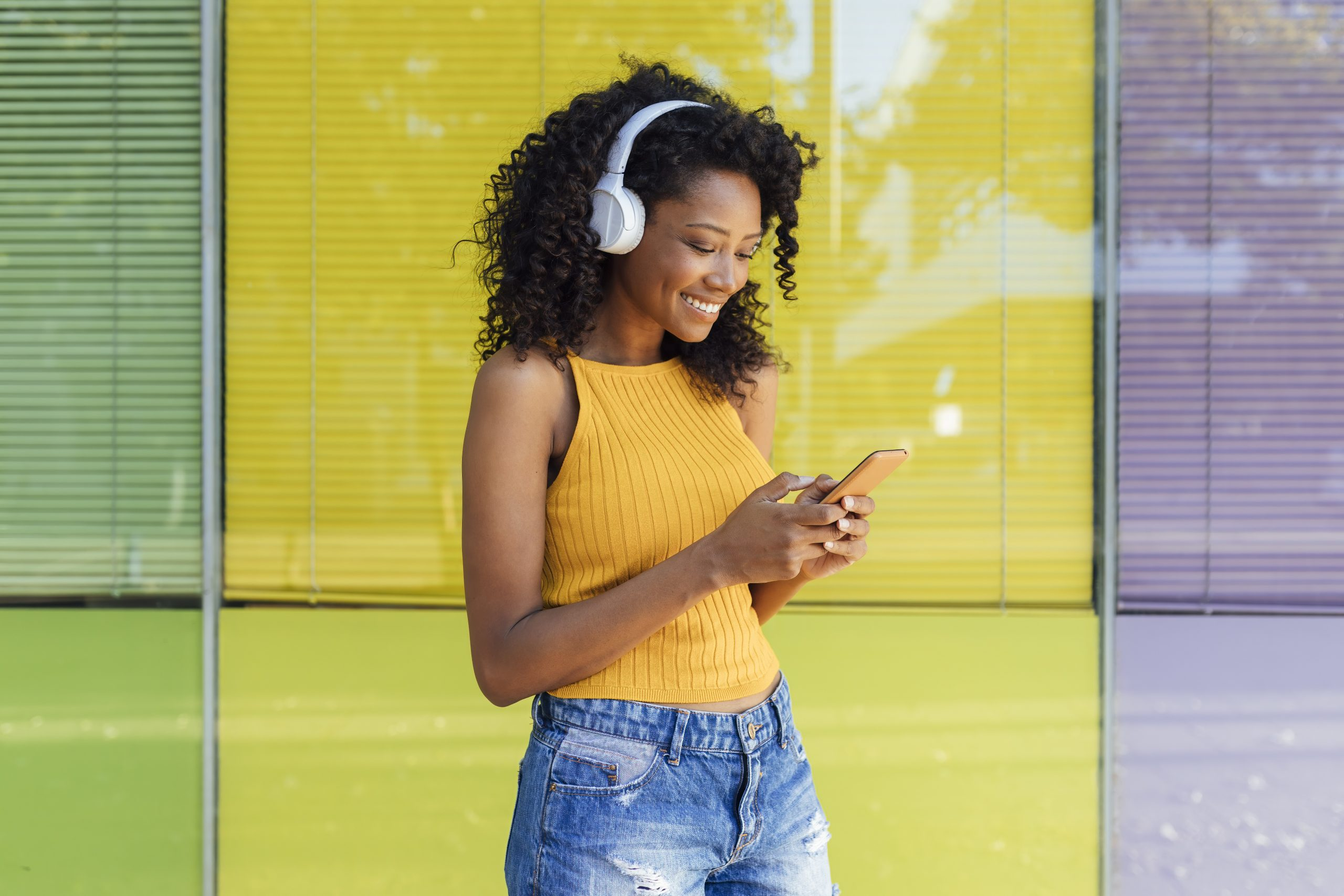 Smiling young woman text messaging through smart phone while standing in front of yellow window