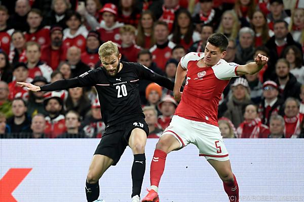 Auf dem Bild sieht man einen österreichischen und einen dänischen Fußballer-Spieler um den Ball kämpfen.